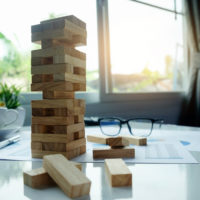 Planning, risk and strategy in business concept, businessman gambling placing wooden block on a tower with meeting background.vintage tone Retro filter effect,soft focus,low light.(selective focus)
